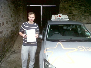 Jake with his Practical Driving Test Pass Certificate in Burtle sheltering from the rain!