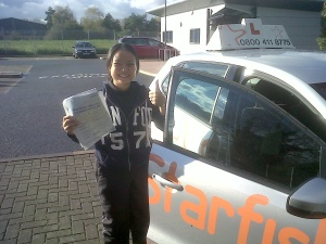Cynthia with her Practical Driving Test Pass Certificate outside Taunton Driving Test Centre.