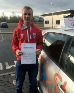 Robbie with his Practical Driving Test Pass Certificate outside Taunton Driving Test Centre